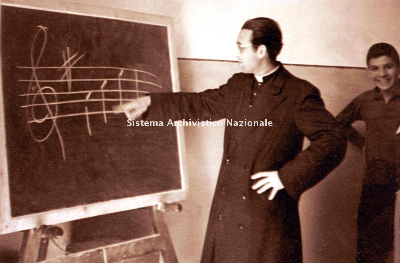 Pietro Allori durante una lezione di musica, sec. XX seconda meta' (Archivio storico diocesano di Iglesias, Fondo Pietro Allori)